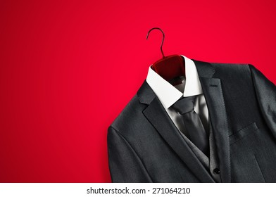 Elegant dark grey mans suit on clothes hanger in bottom right corner on red background.
