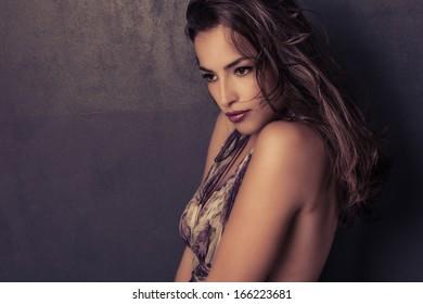 elegant dark hair sensual young woman portrait, muted colors, studio shot