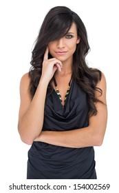 Elegant dark haired model posing with finger on her cheek on white background