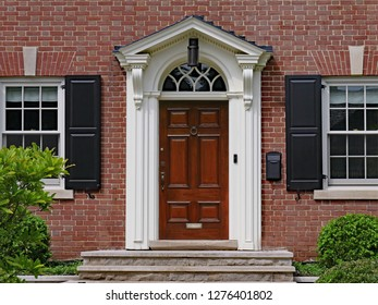 elegant dark wood door of brick house