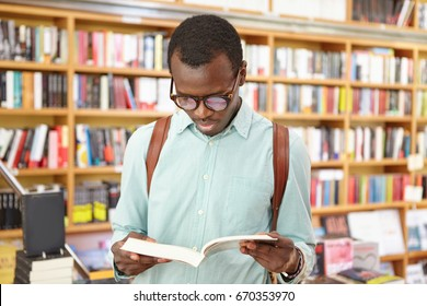 Elegant dark-skinned male wearing shirt and glasses holding rucksack on back reading book while standing in library against bookshelves. College male student preparing for exams in reading hall