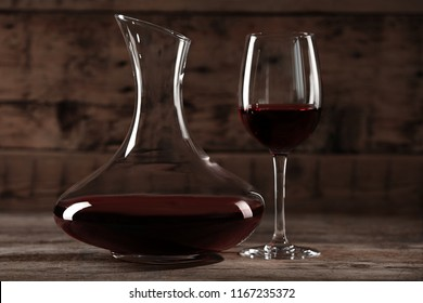 Elegant decanter and glass with red wine on wooden table