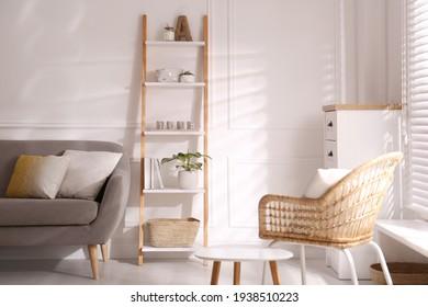 Elegant decorative ladder near sofa in living room - Shutterstock ID 1938510223