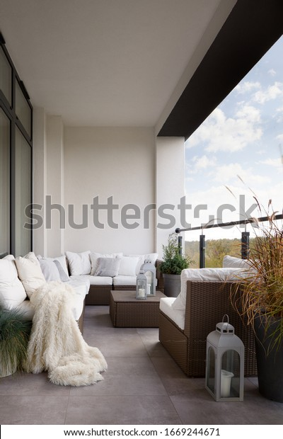 Elegant designed balcony with stylish rattan furniture and many comfortable pillows and blanket