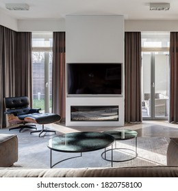 Elegant designed living room with big tv screen, modern fireplace and many window doors