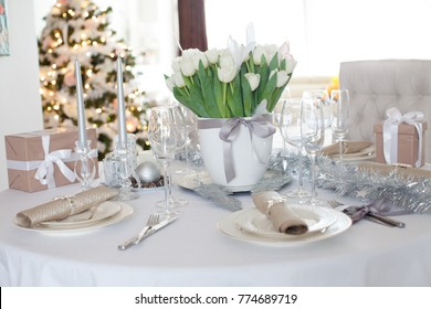 Elegant dining table with presents and Christmas tree in living room