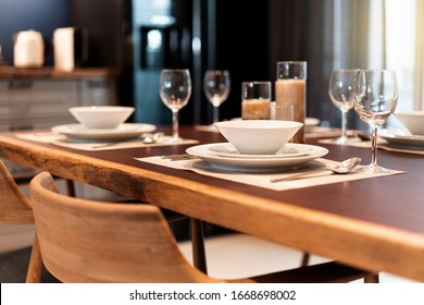Elegant dinner table setting on a wooden table with dinnerware, silverware, utensil, wine glasses and candles. Table set for fine dining, luxury meal hotel service.