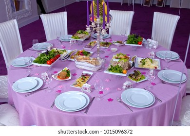 The elegant dinner table. Wedding table decorated with candles, served with cutlery and crockery and covered with a tablecloth . Pink tablecloth . White chairs . A table decorated with balloons.