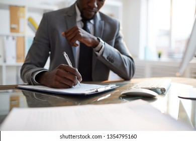 Elegant director of business company or economist with pen putting his signature on paper while sitting by desk