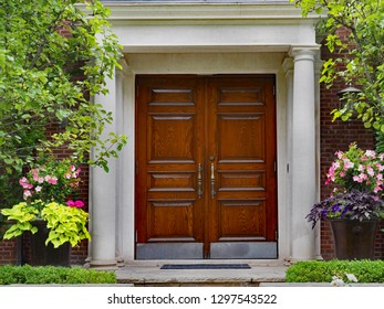 elegant double wooden front door and portico entrance surrounded by flowers of upper class house