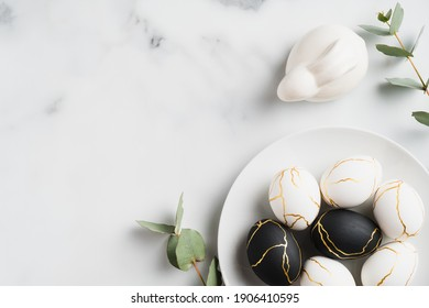 Elegant Easter flat lay composition. Black and golden Easter eggs, rabbit bunny, eucalyptus leaves on marble background. Top view with copy space. Happy Easter concept. Minimal style.