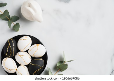 Elegant Easter flatlay composition. Luxury Easter eggs decorated with gold, rabbit bunny, eucalyptus leaves on marble table. Flat lay, top view - Shutterstock ID 1906667086
