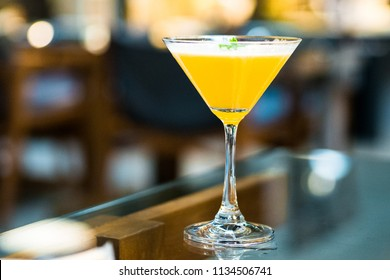 Elegant eggnog yellow passion fruit cocktail in martini glass garnished with basil on glass table