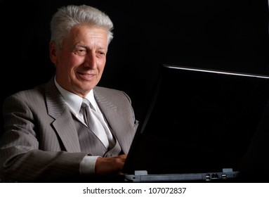 Elegant elderly man in suit on black background
