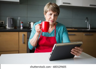 Elegant elderly woman using  tablet and drink tea in the kitchen