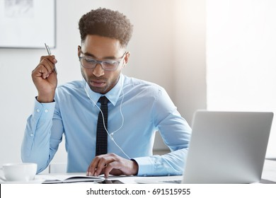 Elegant employee with concentrated look holding pen in hand while writing something looking at his notebook, planning his schedule and meeting with business partenrs, listening to music with earphones