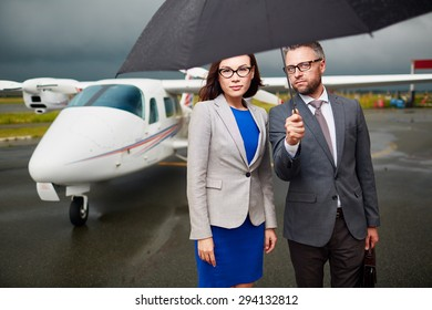 Elegant employees under umbrella looking at camera on rainy day on background of airplane
