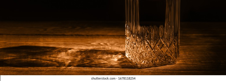 An elegant empty carafe, on a textured wooden table. Decanter in dark style.