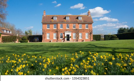 Elegant English Country Manor mansion house Grade 2 listed Victorian period property in red brick. Front view with large garden, green lawn and daffodils