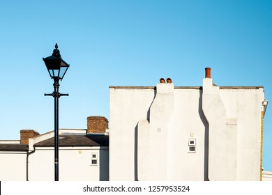 Elegant English simple white wall facade with two chimneys, street lamp and clean blue sky in London, UK