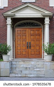 Elegant entrance with wood grain double door and portico