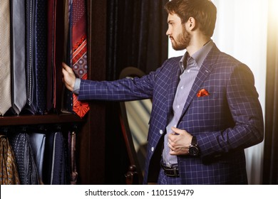 Elegant European Man choosing necktie or tie to match his suit in custome made garment fashion boutique