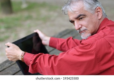 elegant European man in his fifties,sitting at the park, holding a computer with his hands.Outdoors business man portrait