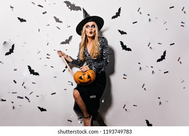 Elegant evil wizard holding aspen stake and pumpkin. Indoor portrait of cheerful vampire posing with bats on background.
