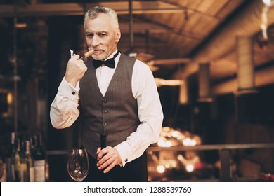 Elegant experienced sommelier uncorking bottle of wine in restaurant. Wine tasting. Sommelier tasting wine in restaurant.