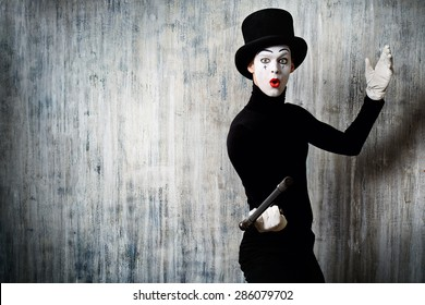 Elegant expressive male mime artist posing with walking stick by a grunge wall. - Shutterstock ID 286079702