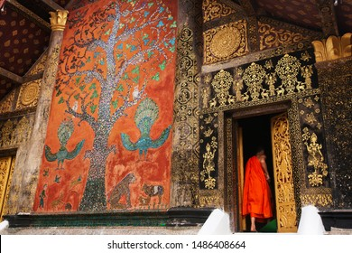 Elegant exterior of ancient temple of Wat Xieng Thong, magical stained glass on wall, young Laotian Buddhist monk stands at the door. Luang Prabang, Laos. The temple is open to the public.