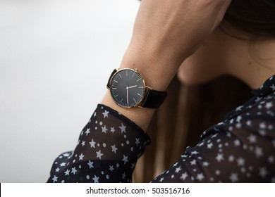 elegant fall outfit. closeup of black wrist watch on the hand of stylish woman. fashionable girl on the street. female fashion blogger.