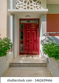 elegant family house entrance with dark red door and plants, Athens Greece