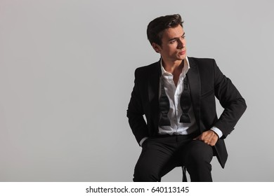 elegant fashion model sitting and looks to side on grey background