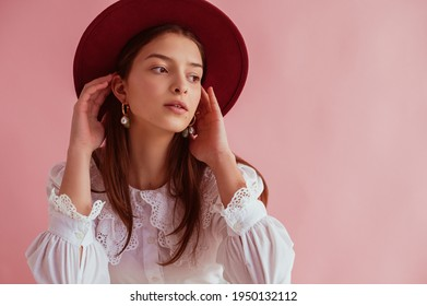 Elegant fashionabel woman wearing stylish dark red hat, pearl earrings, white vintage blouse, posing on pink background. Copy, empty space for text