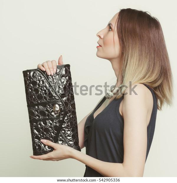 Elegant fashionable woman with leather handbag. Stylish girl holding black bag. Female fashion vogue. Studio. Side profile view.