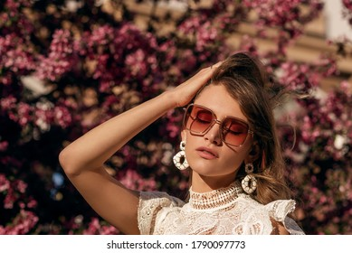 Elegant fashionable woman wearing trendy luxury oversize sunglasses, big white earrings, posing at sunset in street. Copy, empty space for text