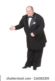 Elegant fat man in a dinner jacket and bow tie smiling charmingly as he holds out his hand to the side gesturing in that direction