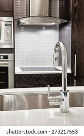 Elegant faucet and sink in island counter of modern kitchen