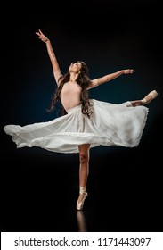elegant female ballet dancer in white skirt dancing on dark background