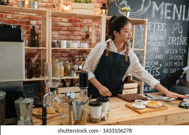 elegant female barista preparing customer meal in bar counter at modern cafe. young girl coffeehouse staff ready for hot coffee and croissant pressing ring. worker ringing service bell calling waiter