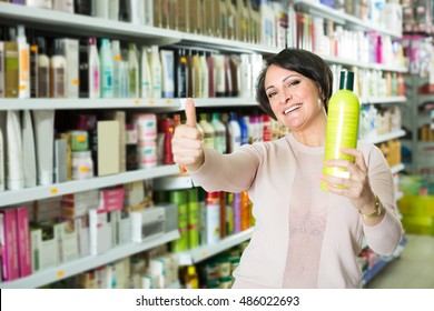 Elegant female customer buying conditioner for hair in cosmetology
