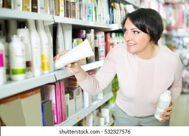 Elegant female customer buying conditioner for hair in supermarket