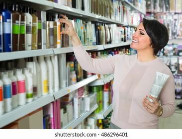 Elegant female customer buying mask for hair in supermarket