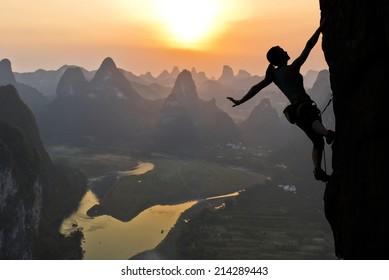 Elegante silhueta de alpinista extremo contra o pôr do sol sobre o rio. China, paisagem típica chinesa com montanhas e rio.