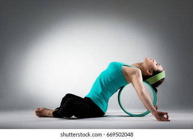 elegant female gym player lying on pilates ring stretching body meditation workout softness when she sitting in grey wall background.