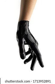 Elegant female hand in black latex glove on a white background. Female hand in liquid black oil or black acrylic paint