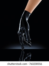 Elegant female hand in black latex glove on a black background. Female hand in liquid black oil or acrylic paint