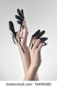 Elegant female hands, fingers dipped in black paint or latex on a light background