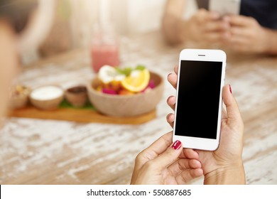 Elegant female hands with neat red nails using white mobile phone, viewing newsfeed via her account on social networks, liking pictures and reading posts of her friends during lunch at cafeteria